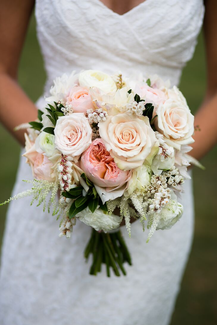"""""""I am a traditional girl who loves textures,"""" Caitlin says. """"The flowers had lots of depth and shape."""" The couple's florist from Beautiful Days complemented their natural farm setting with a stunning bouquet filled with pink hues and lush greenery. A mixture of ivory and blush roses, pink garden roses, Japanese pieris, white ranunculus and white astilbes were included in the arrangement."""