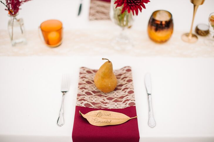 Even the escort cards felt like fall. Shelby made one for every guest by spray-painting magnolia leaves gold and then writing every guest's name. They were placed near Bosc pear wedding favors.