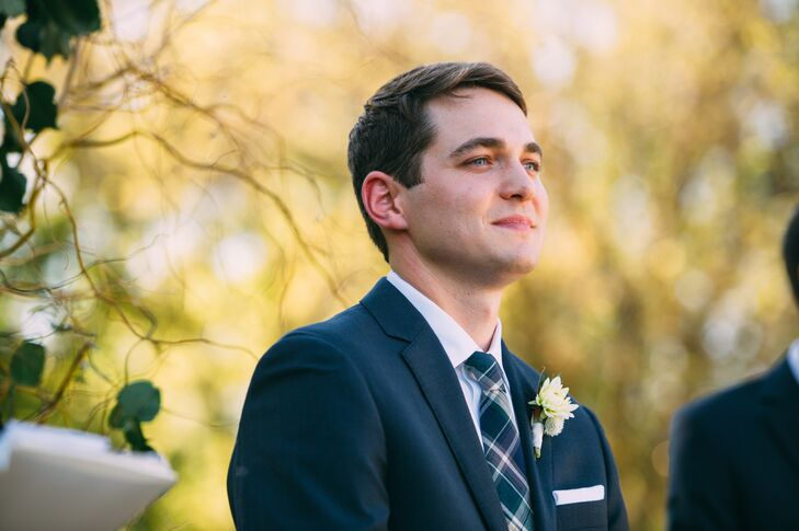Ryan wore a navy suit with a plaid tie on his wedding day. He also wore a white boutonniere with chrysanthemum, dahlia and his favorite herb, rosemary.