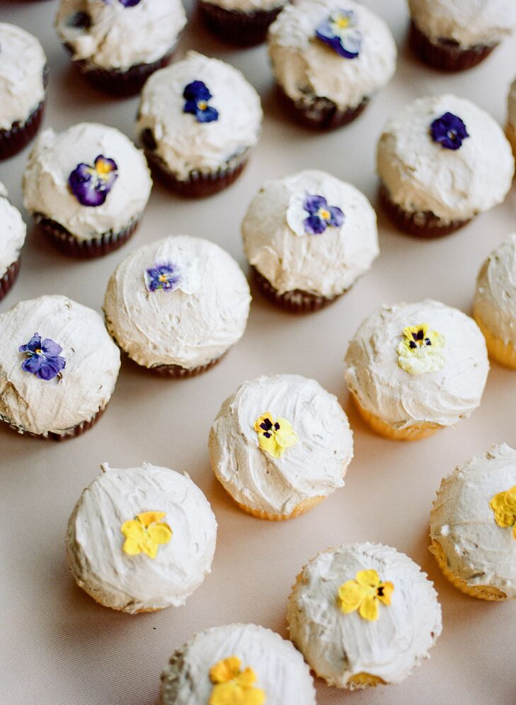 An assortment of small flavored cupcakes were topped with dried edible flowers to differentiate the flavors.