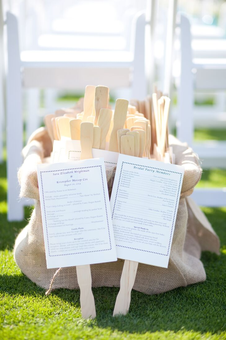 Guests grabbed white ceremony programs attached to wooden sticks, using the ceremony props as fans for the hot summer day.