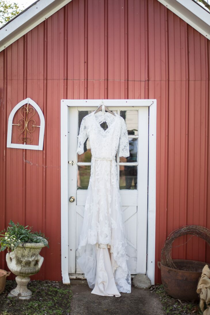 3cf18a59868 The Bride s Lace 3 4 Sleeve Wedding Dress Hanging on the Barn Door