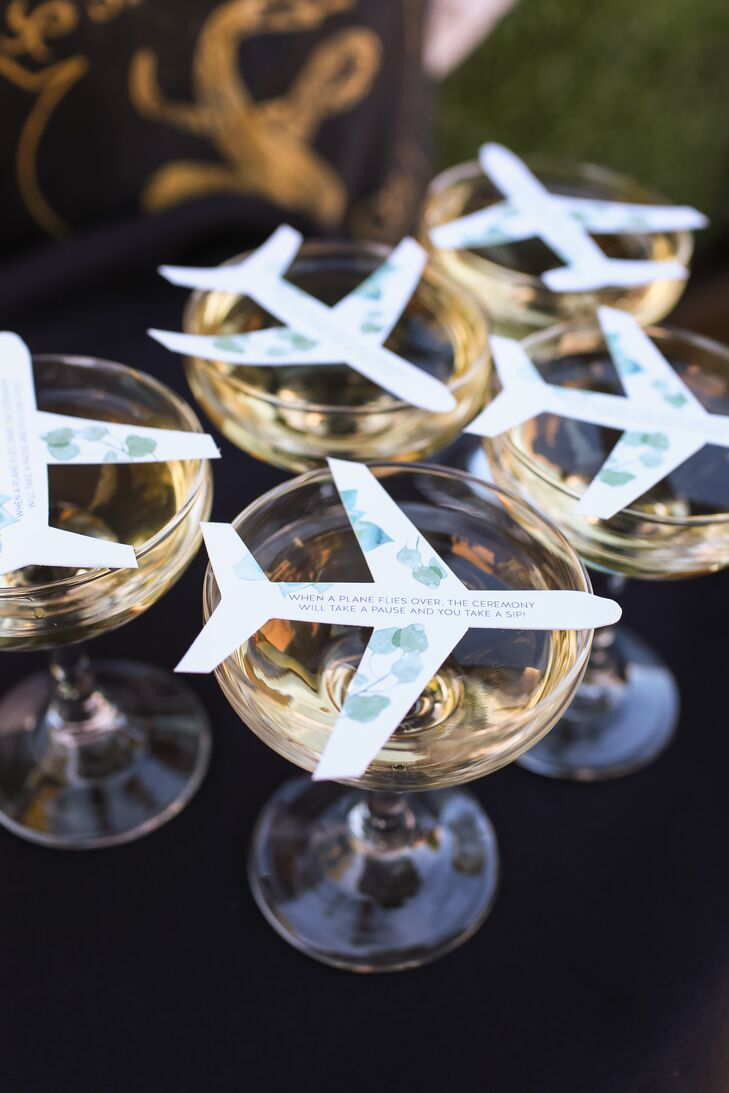 """Our venue was right by the airport, so we knew we'd have a few interruptions during the ceremony with the planes flying overhead,"" Andrea says. ""With an 'If you can't beat them, join them' mentality, we turned the disruption into a positive. We handed guests glasses of champagne as they arrived to the ceremony, and on top of the glass was a cutout of an airplane that said 'When a plane flies over, the ceremony will take a pause and you will take a sip!' It made the pauses in the ceremony a fun celebration for all."""