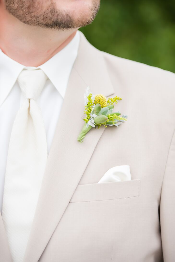 Nolan had a boutonniere arranged with succulents and yellow brunia pinned to his tan lapel jacket. He wore a white tie over his white collared dress shirt, which matched his pocket square. The groomsmen matched Nolan with their suits and boutonnieres, but had yellow ties instead of white.