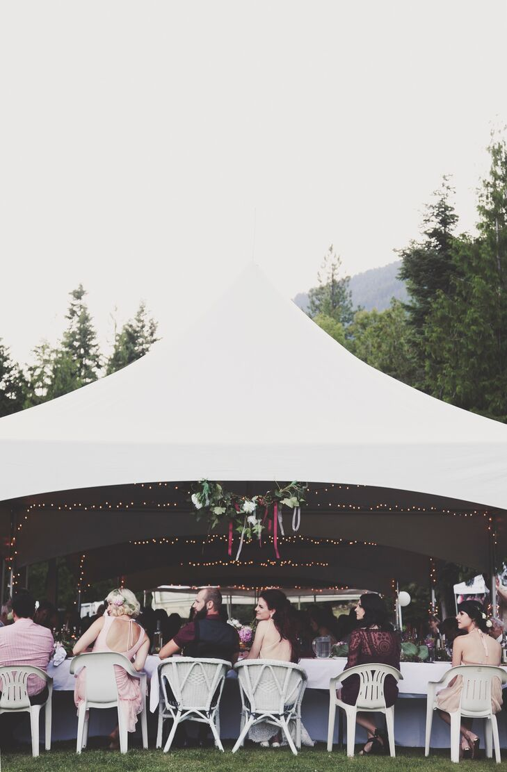 The reception was held under a tent that was decorated with string lights, white and burgundy ribbons and greens.