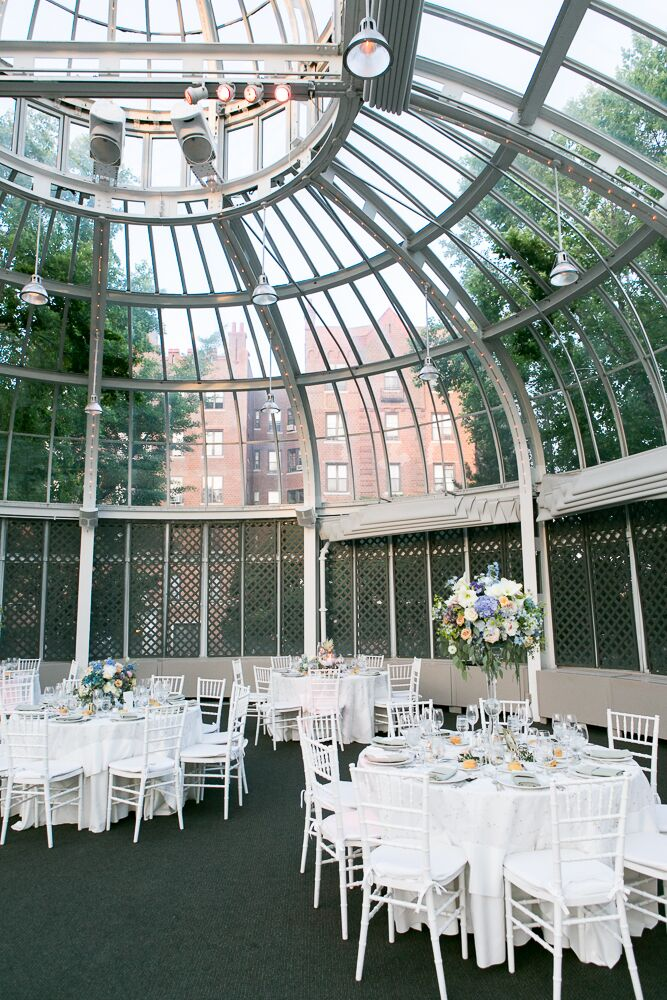 Alexandra and Will's whimsical vintage inspire wedding reception took place in the Palm House at the Brooklyn Botanic Garden and was decorated with white round tables, white chiavari chairs and floral centerpieces of roses, peonies and hydrangeas in alternating heights.