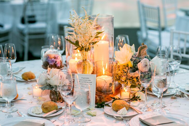 """Alexandra and Will's wedding florist, Rebecca Shepherd Floral designs, decorated the reception table centerpieces with various flowers, including roses, peonies and irises, and warm candlelight. """"She used bell jars and antique candlesticks to add to the centerpieces,"""" Alexandra says."""