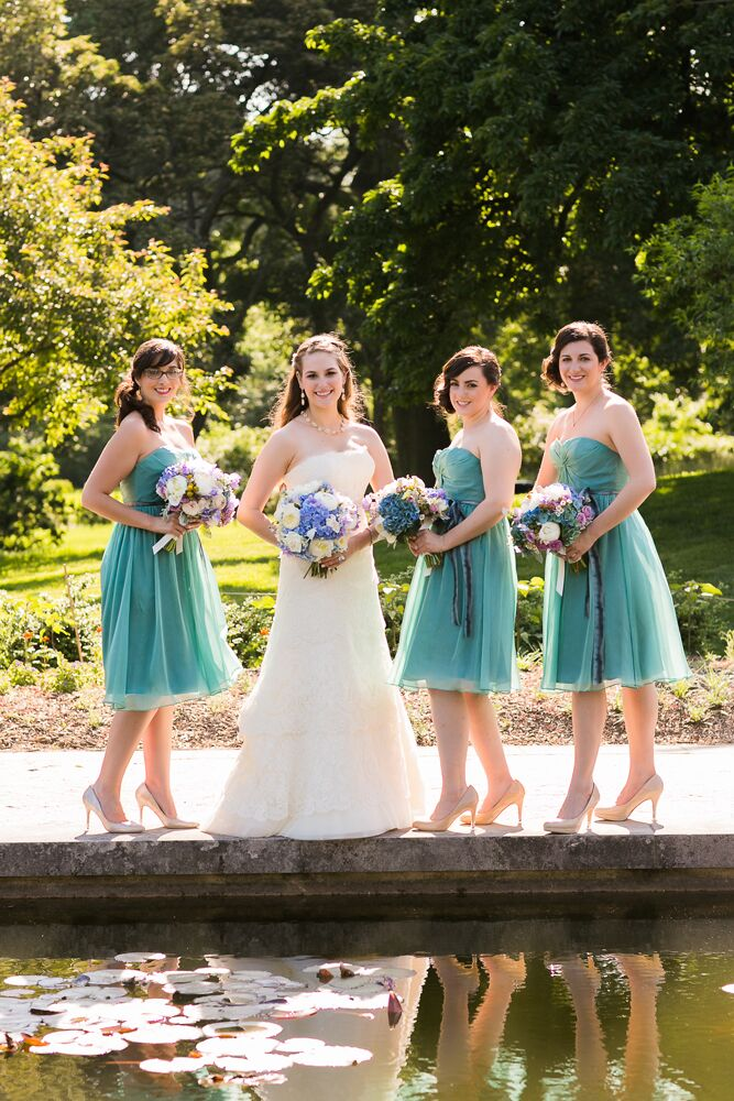 """Alexandra's bridesmaids wore knee-length, green chiffon dresses from Bella Bridesmaids. """"Initially I was going to let my bridesmaids choose their own style of dress in the same color and fabric, but in a happy accident, all three chose the same dress,"""" Alexandra says."""