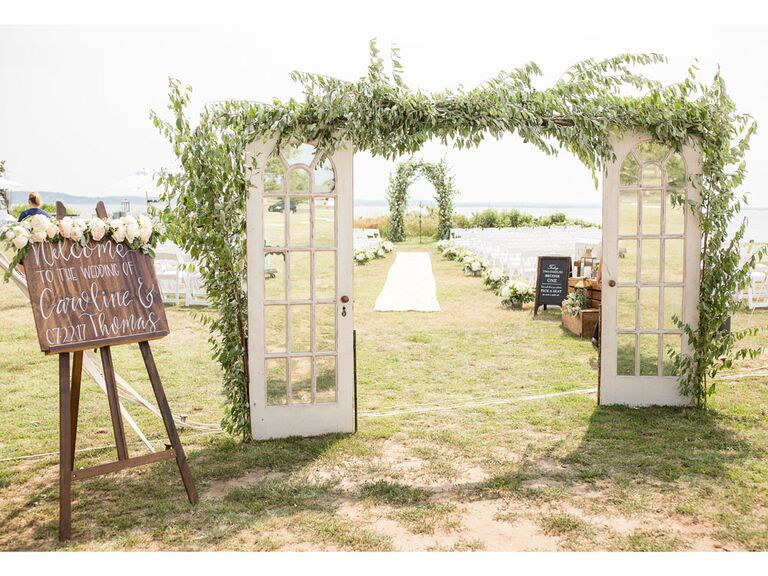 Vintage distressed French door archway covered in greenery leading to ceremony aisle