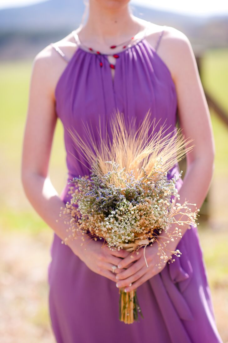 The bridesmaids carried rustic dried grass, baby's breath and wheat grass bouquets with their mixed purple dresses.