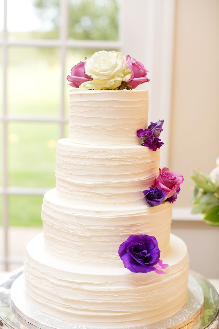 A four-tiered cake frosted in vanilla cream and adorned with purple flowers was simply elegant.