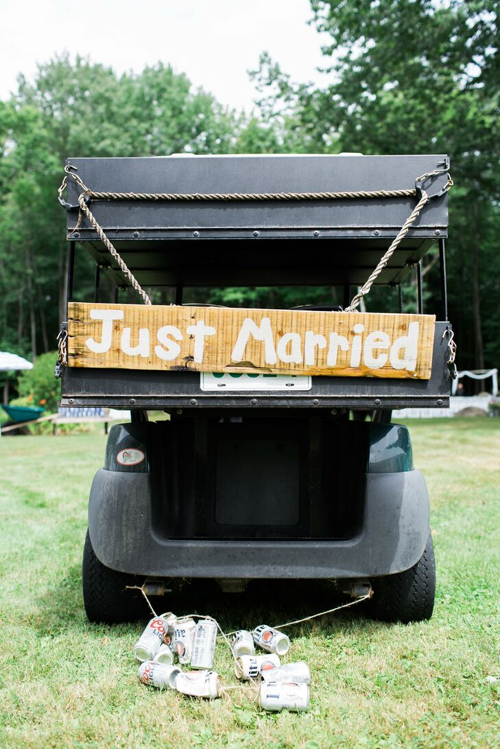 "After cocktails and photos on the waterfront, Liz, Boris and their wedding party hopped in golf carts—the newlyweds' tricked out with a classic string of cans and a wooden ""Just married"" sign—and rolled into cocktail hour in style."