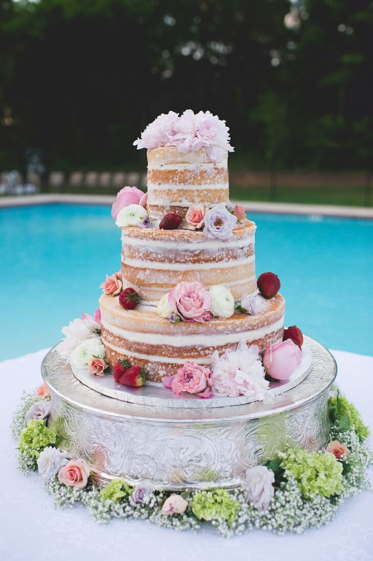 The naked wedding cake revealed multiple layers of buttermilk vanilla cake filled with mascarpone cheese icing, strawberries and jam. Scattered strawberries and soft pink, lavender, red and white flowers decorated the tiers for a fresh, garden-inspired style.