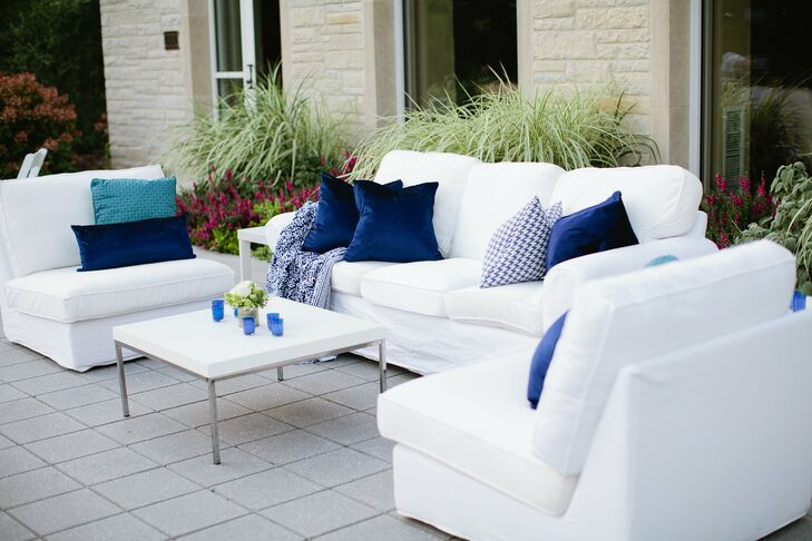 White seating accented with navy throw pillows provided guests a place to relax during cocktail hour.