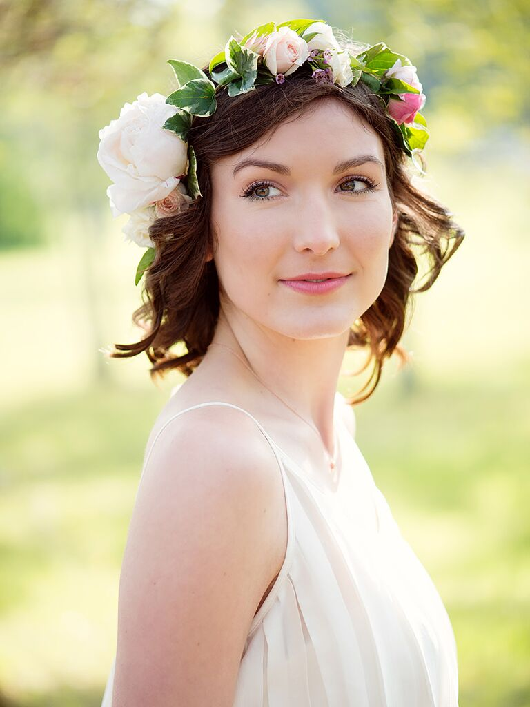 Short curly wedding hairstyle with an ivy and rose flower crown