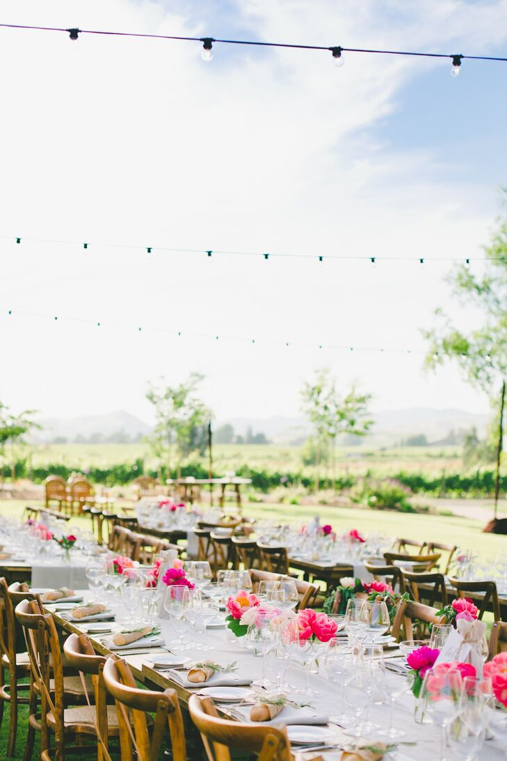 "With Etude Winery providing a beautiful natural backdrop for their ""I do's,"" Robyn and Tony decided to keep the decor on the more understated side and selected a palette of soft neutrals to play up the lush setting and distant mountain views. For the reception, wooden farm tables and French country chairs, ivory linens and a wine barrel bar played up the organic feel of the venue's surroundings, while small arrangements of peonies, ranunculuses and garden roses in vibrant pink and red hues added a pop of fresh color to the decor."