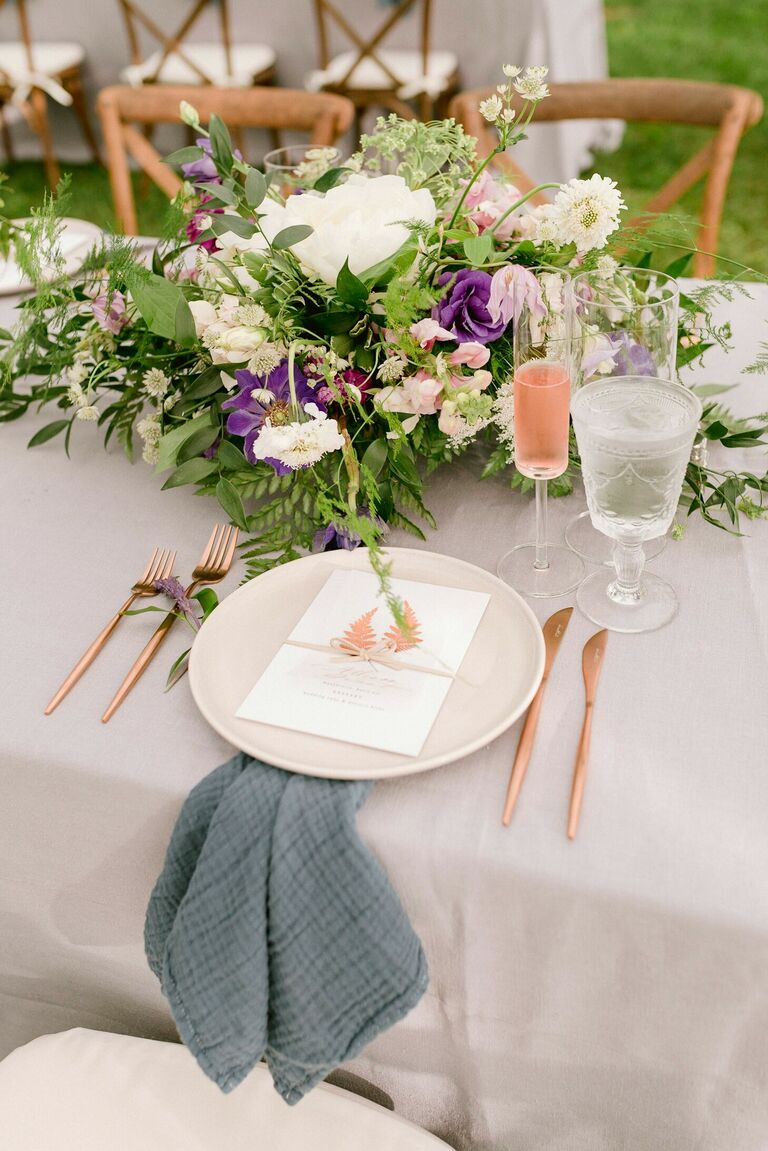Romantic place setting with fern-centric centerpieces and blue napkins