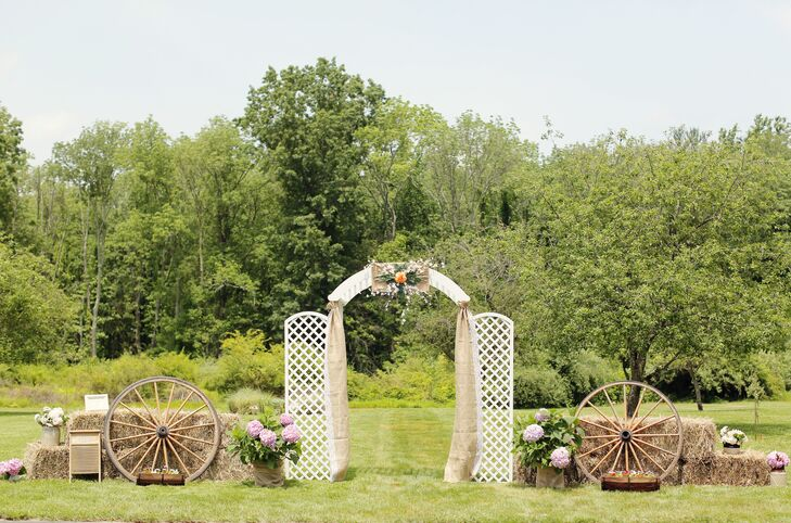 Kathleen and Kenny exchanged their vows in true country style, under a ceremony arch draped in burlap, which was surrounded by hay bales and wagon wheels.