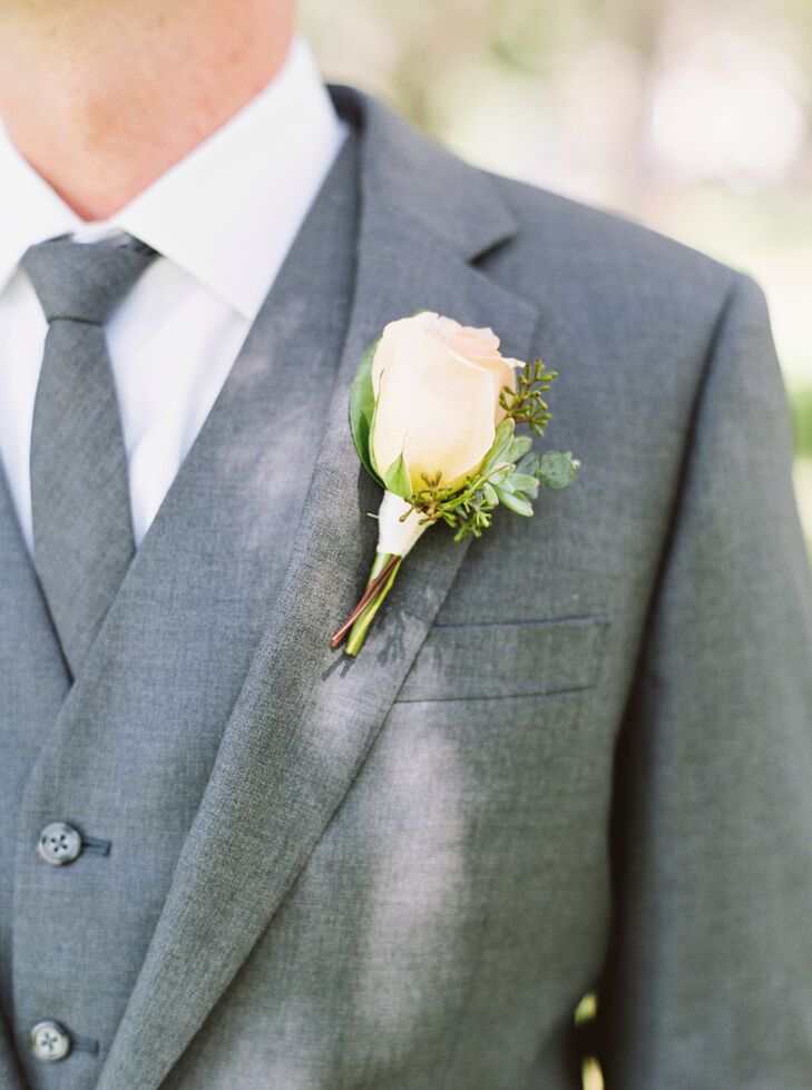Adding some color to his charcoal and white suit, Brian chose a peach rose boutonniere to top his notched lapel. The same-style rose was used throughout the bridal party's bouquets as well as the tablescape on their head table.