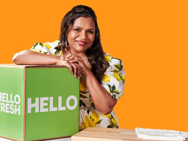 Mindy Kaling smiling and leaning over Hello Fresh delivery box