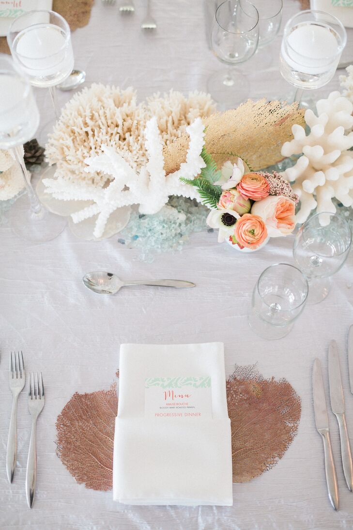 "Their 20-foot head table was filled with tokens from the sea. ""I'm so obsessed with how it turned out,"" Stephanie says. Centerpieces of actual sea coral in white and neutral tones, as well as sea fans and blue sea glass, formed the tablescape. It didn't stop there. Guests' napkins were placed on sea fans for an unexpected twist."