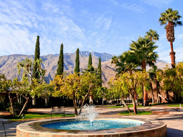 Fountain and trees and mountains in background in Palm Springs