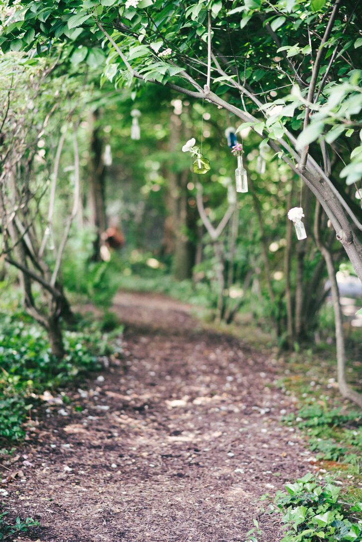 Little bottles of lavender hung from trees along a wooded path, leading to the ceremony site, creating a romantic vibe.