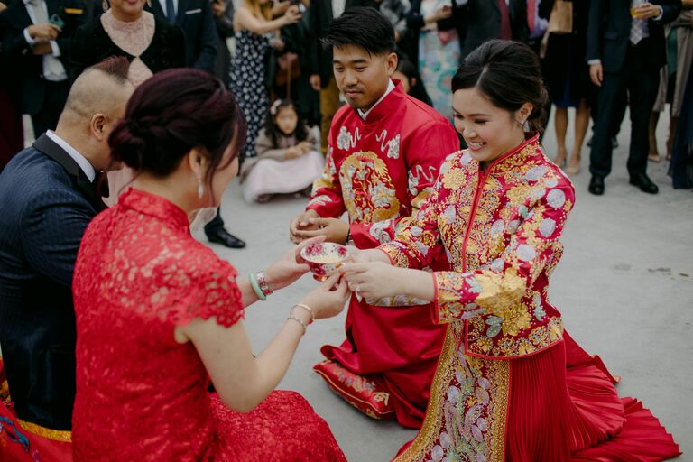 Couple serving tea to parents during Chinese wedding tea ceremony