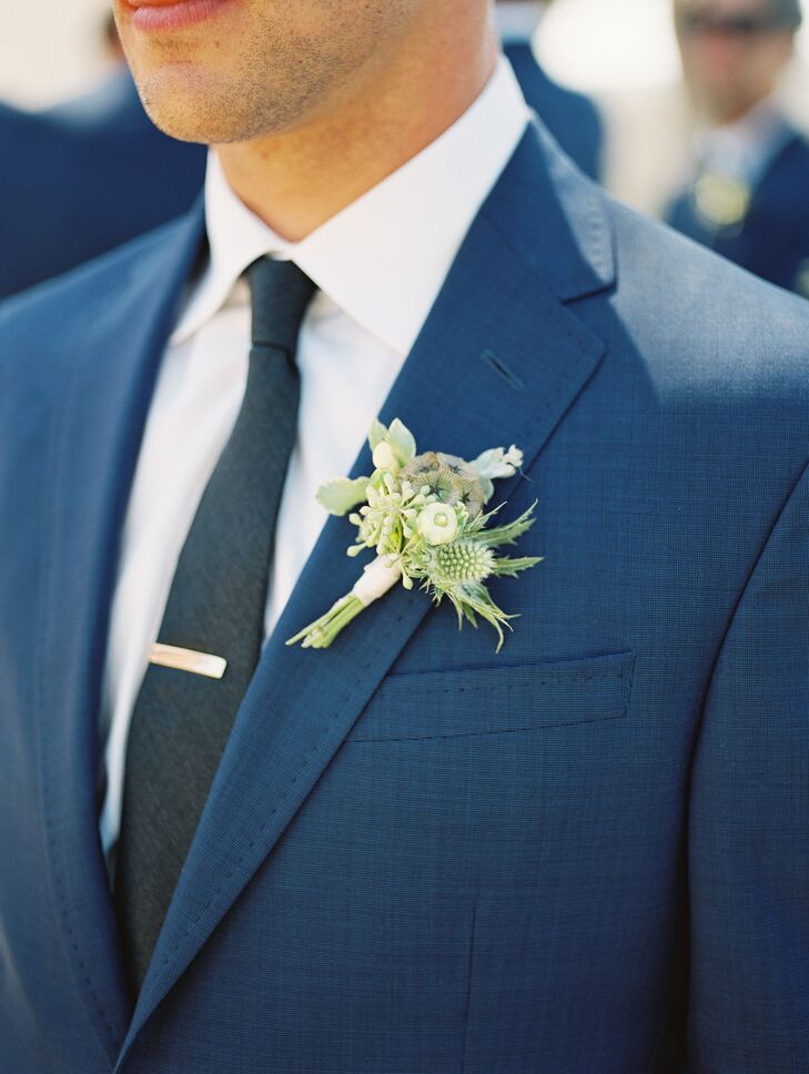 Cutter paired his midnight blue Tom Ford suit with a sleek black tie. His boutonniere was made with white ranunculus and textured greenery.