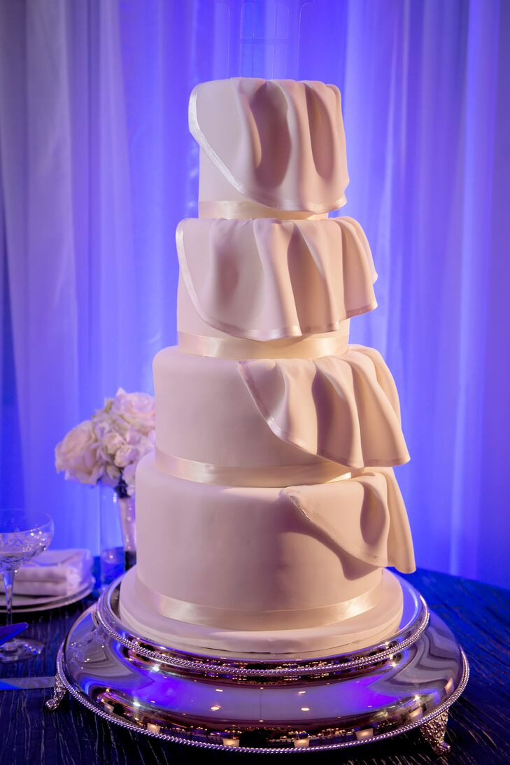 """The newlyweds' cake took inspiration from Angela's tiered wedding dress, and was topped with a custom """"H."""" The couple cut their cake as Ed Sheeran's """"Thinking Out Loud"""" played in the background."""