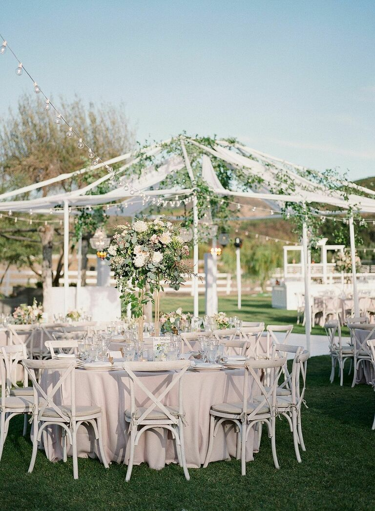 Outdoor wedding reception with neutral color palette and greenery