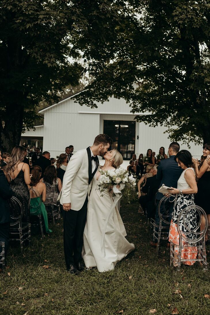 Bride and Groom Share Kiss During Wedding Recessional