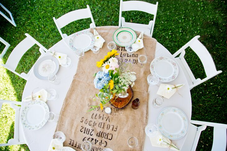 Tables were set with burlap table runners, mix-matched vintage plates and  local flower arrangements set atop handmade wood slabs.