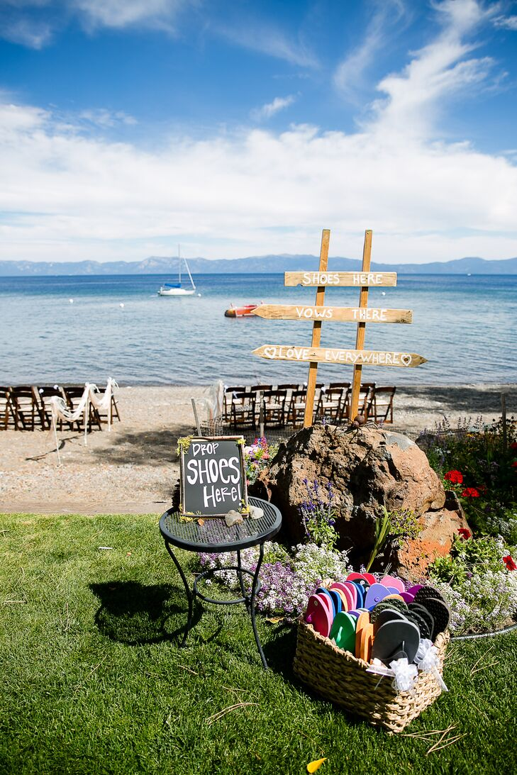 """Before stepping on the sand where the ceremony took place, a bin of flip-flops were arranged for guests to change into the casual footwear. Next to the shoes was a chalkboard sign that read """"Drop shoes here"""" and a wooden sign that read """"Shoes here, vows there, love everywhere."""""""