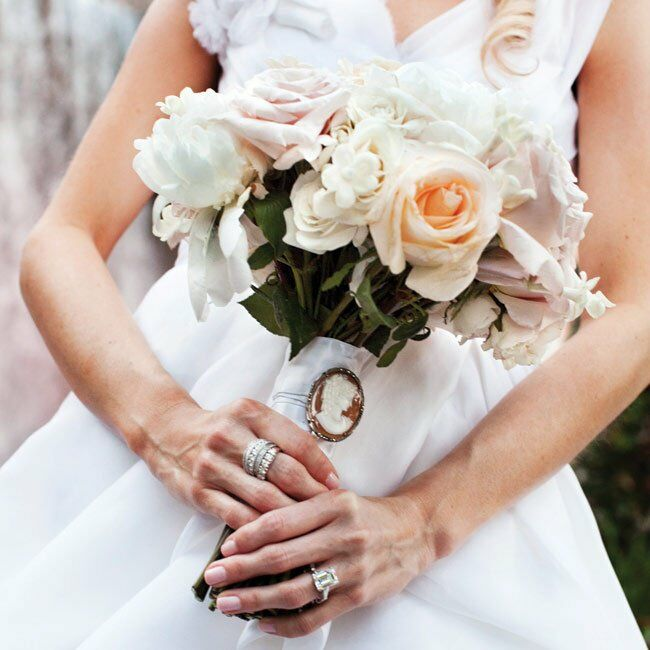 For a totally traditional arrangement, the bride chose white roses, peonies and stephanotis, accented with a vintage brooch.