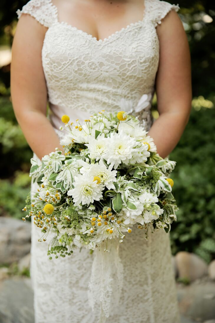 """Holly carried a bouquet of spray daisies, billy balls and green filler. """"I gave our florist creative discretion to come up with something classic, natural, happy, and loose,"""" she says."""