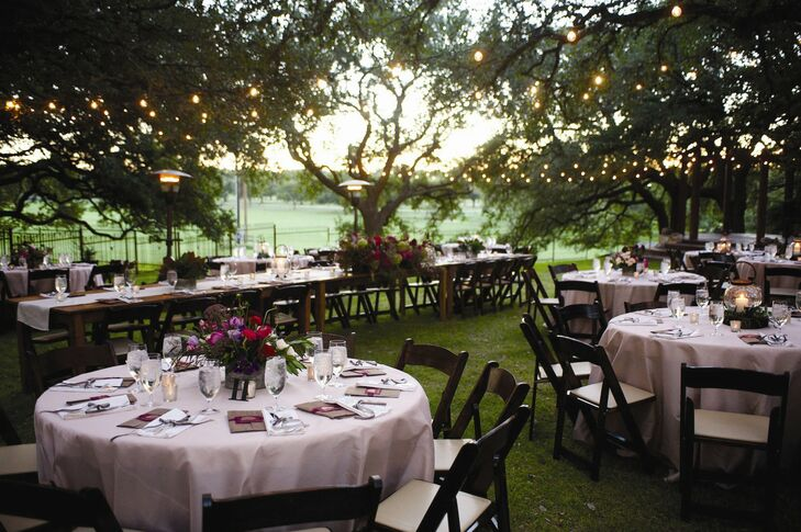 Dark wood reception tables fit seamlessly into the lush outdoor setting. String lights and lanterns upped the romance factor as the sun set.