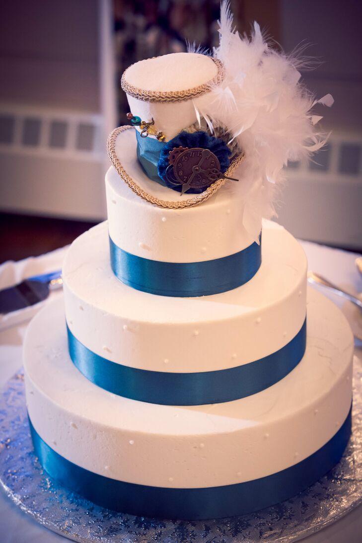 "The three-tier wedding cake was decorated with teal ribbon and a velvet white ""Mad Hatter""-inspired top hat as a cake topper."