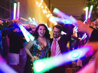 Bride and groom dancing at reception with colored light sticks