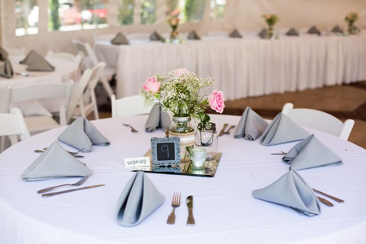 At the white tented reception at Lairmont Manor in Bellingham, Washington, dining tables dressed in white linens had pink rose and baby's breath centerpieces decorating the middle—arranged inside mason jars wrapped with lace that gave off a vintage vibe.