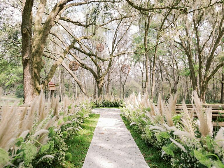 Boho outdoor wedding ceremony venue with pampas grass clusters