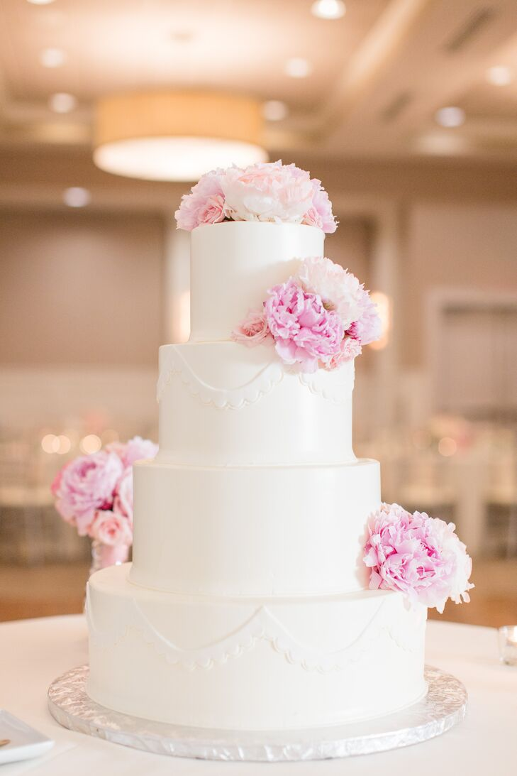 After a dinner of cranberry chicken, grilled Atlantic salmon and seared pork chops, Gina and Steven treated guests to a slice of wedding cake. The four-tiered confection was decorated with fresh pink peonies and fondant draping and boasted espresso-flavored cake with chocolate buttercream.