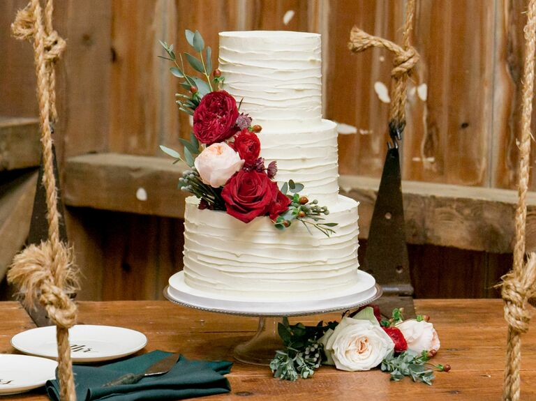 white buttercream wedding cake with red roses