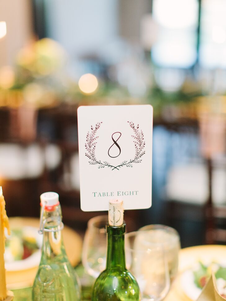 Ann and her family collected several green glass wine bottles months before the wedding, and they used the corks to hold up table numbers decorated with wreath designs.