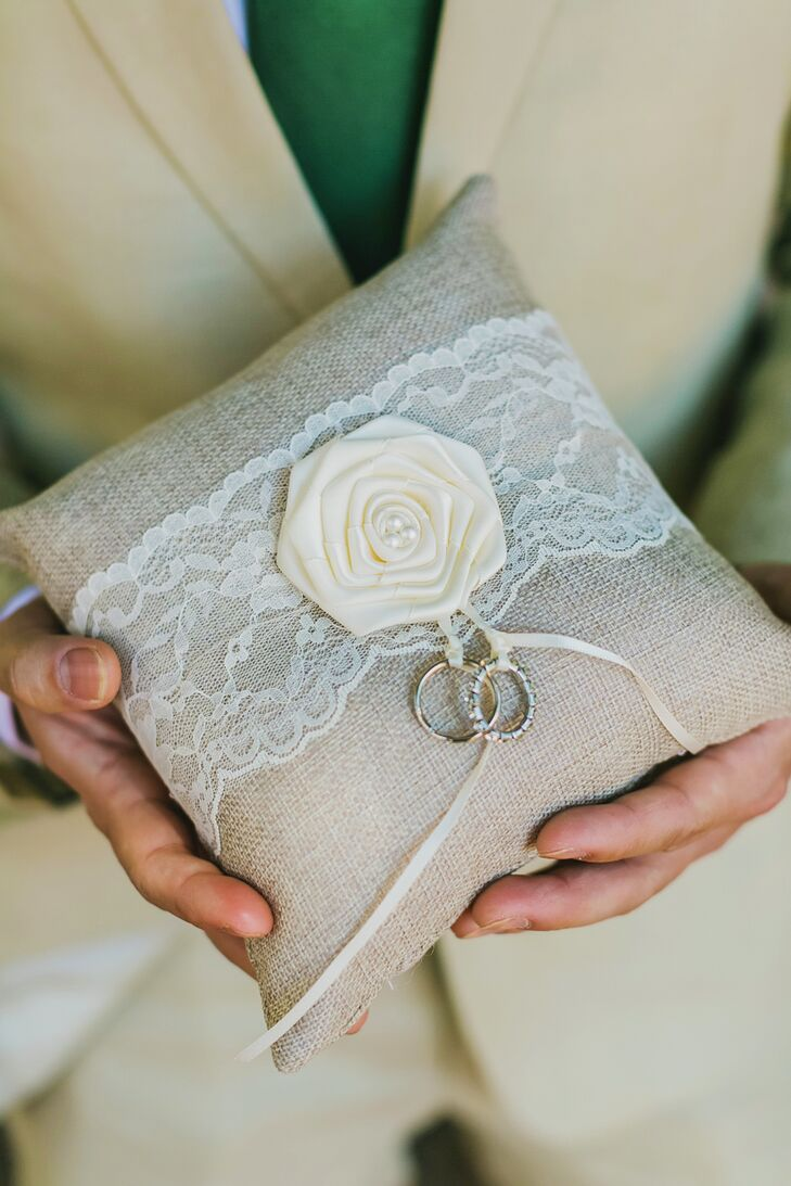 Emily and Vishal's rings were carried on this khaki pillow, decorated with lace (a fabric accent used throughout the event, including as runners on the reception's dining tables).