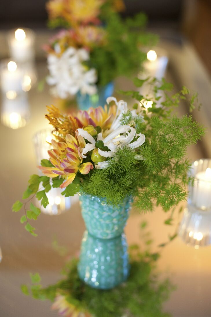 Smaller centerpieces of dahlias, nerine lilies and asparagus ferns were placed in turquoise vases and surrounded by votives.