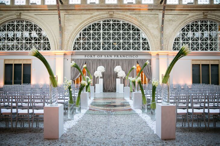 The ceremony took place inside the San Francisco Ferry Building in San Francisco, California, where the stone-tile aisle had tall calla lily arrangements lining its pathway. Courtney and Patrick got married at the front, surrounded by overflowing arrangements of white orchids perched on top of white columns.