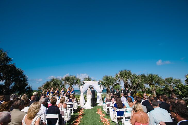 """""""We knew we wanted an outdoor venue overlooking the ocean, and this provided the perfect setting,"""" Ashley says. Their planner from the Dtales helped decorate Ashley and Phil's ceremony at Hammock Beach Resort in Palm Coast, Florida, with all beach-inspired decor. Lanterns filled with sand and seashells marked the waterfront aisle while pink and orange flower petals filled the space below. The rows of white folding chairs and matching wedding arch also helped highlight their natural setting."""