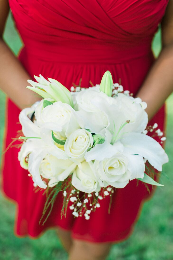 The all-white bridesmaid bouquets contrasted with their bright red dresses. The arrangements by the Blossom Shop included lilies and roses, just as the bride's did.