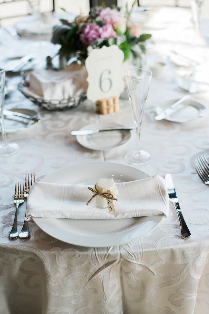 Hand poured candles in small hexagon jars sealed with a linen and mesh fabric top were given to guests as favors.